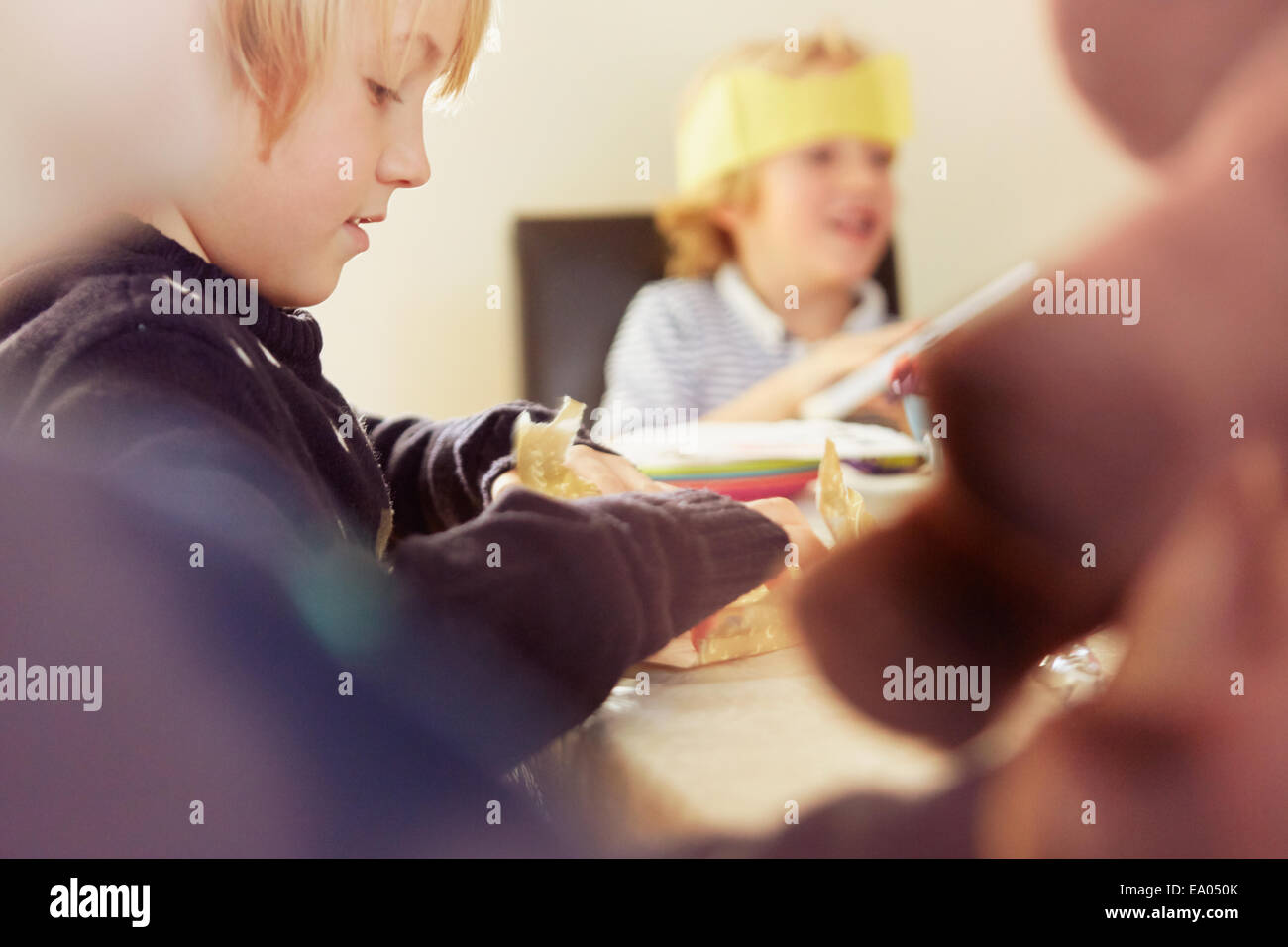 Young boy opening up Christmas present at table - Stock Image