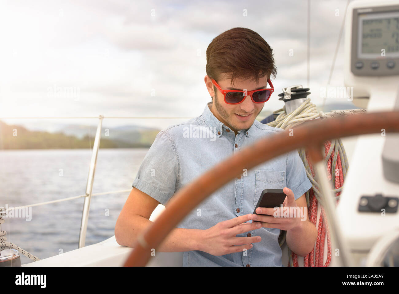 Young man using mobile phone on yacht under sunny sky - Stock Image