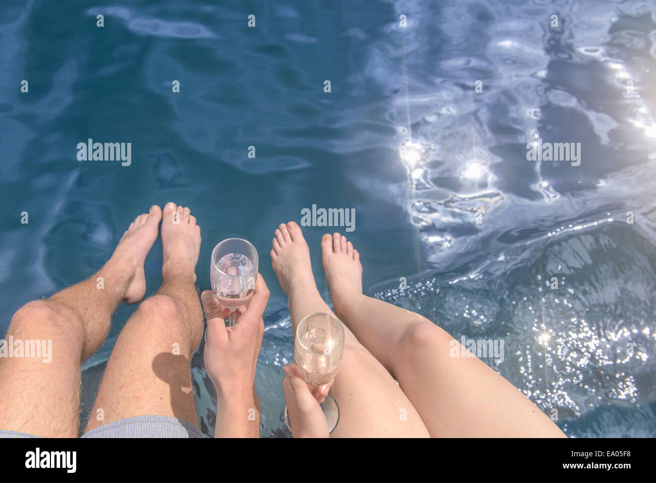 Young barefoot couple holding champagne glasses over sunlit lake, overhead view - Stock Image