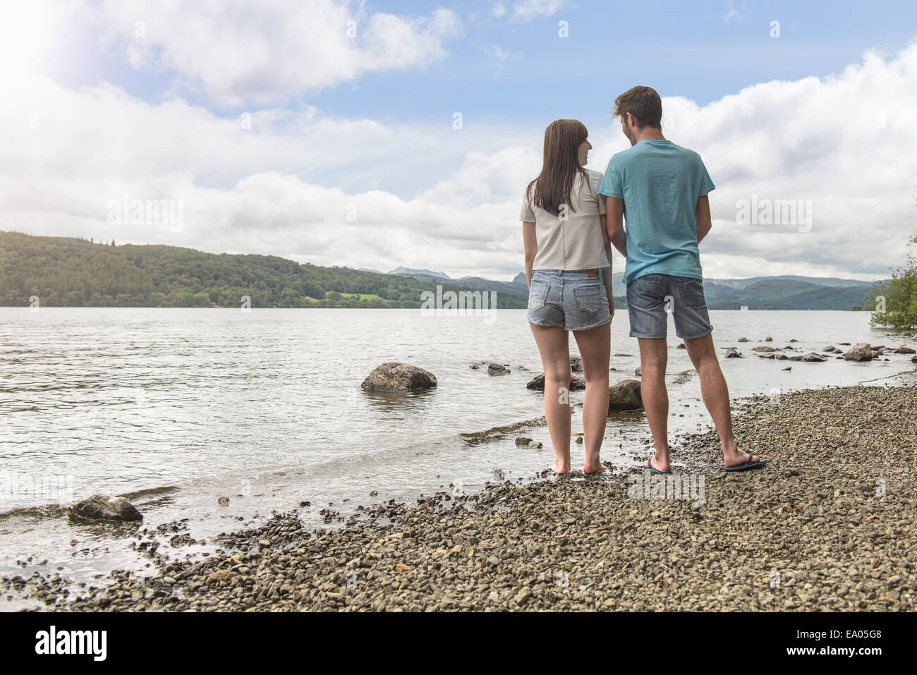 Young couple looking to each other at the edge of lake under sunny sky Stock Photo