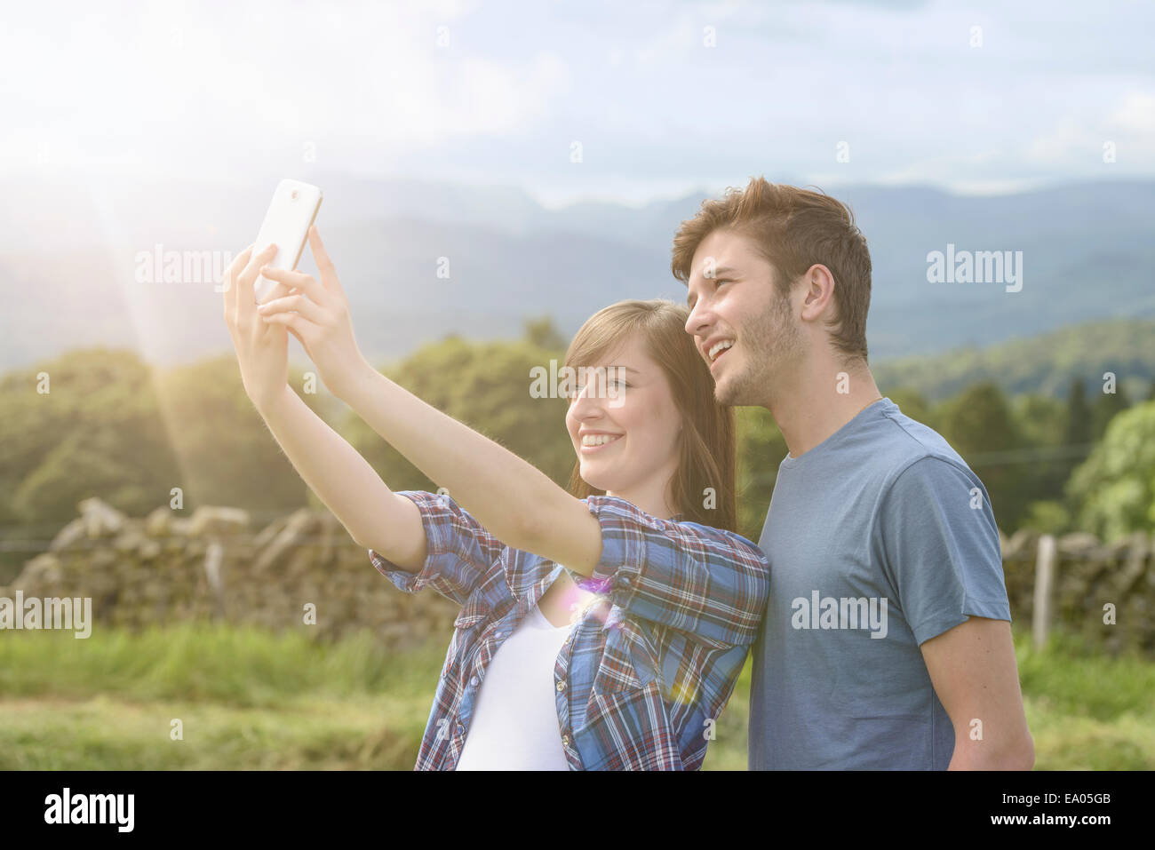 Young couple taking self portrait on mobile phone in countryside under sunny sky - Stock Image