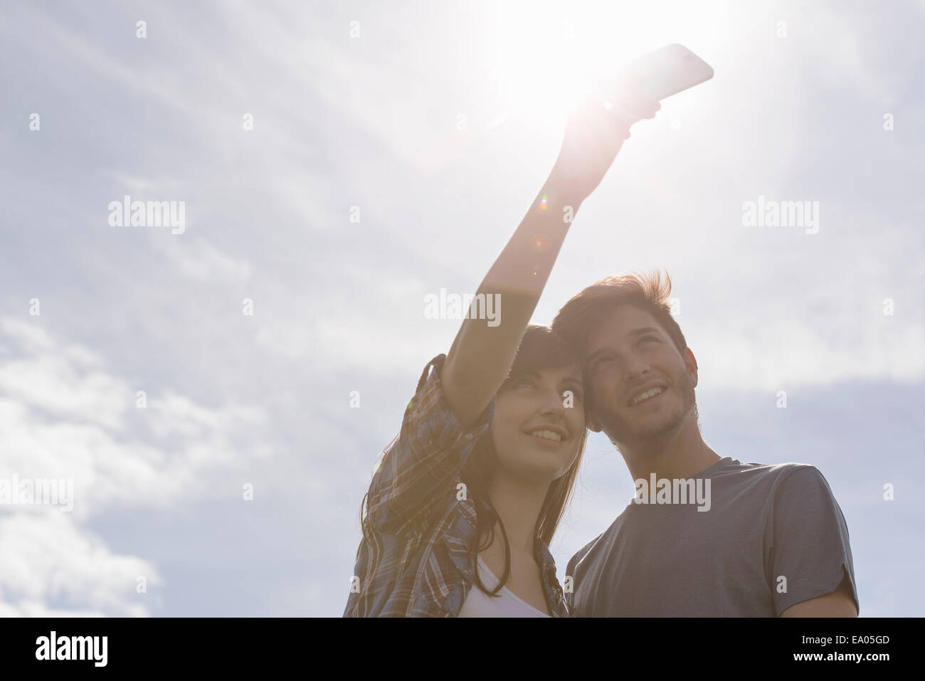 Young couple taking self portrait on mobile phone under bright sunny sky - Stock Image