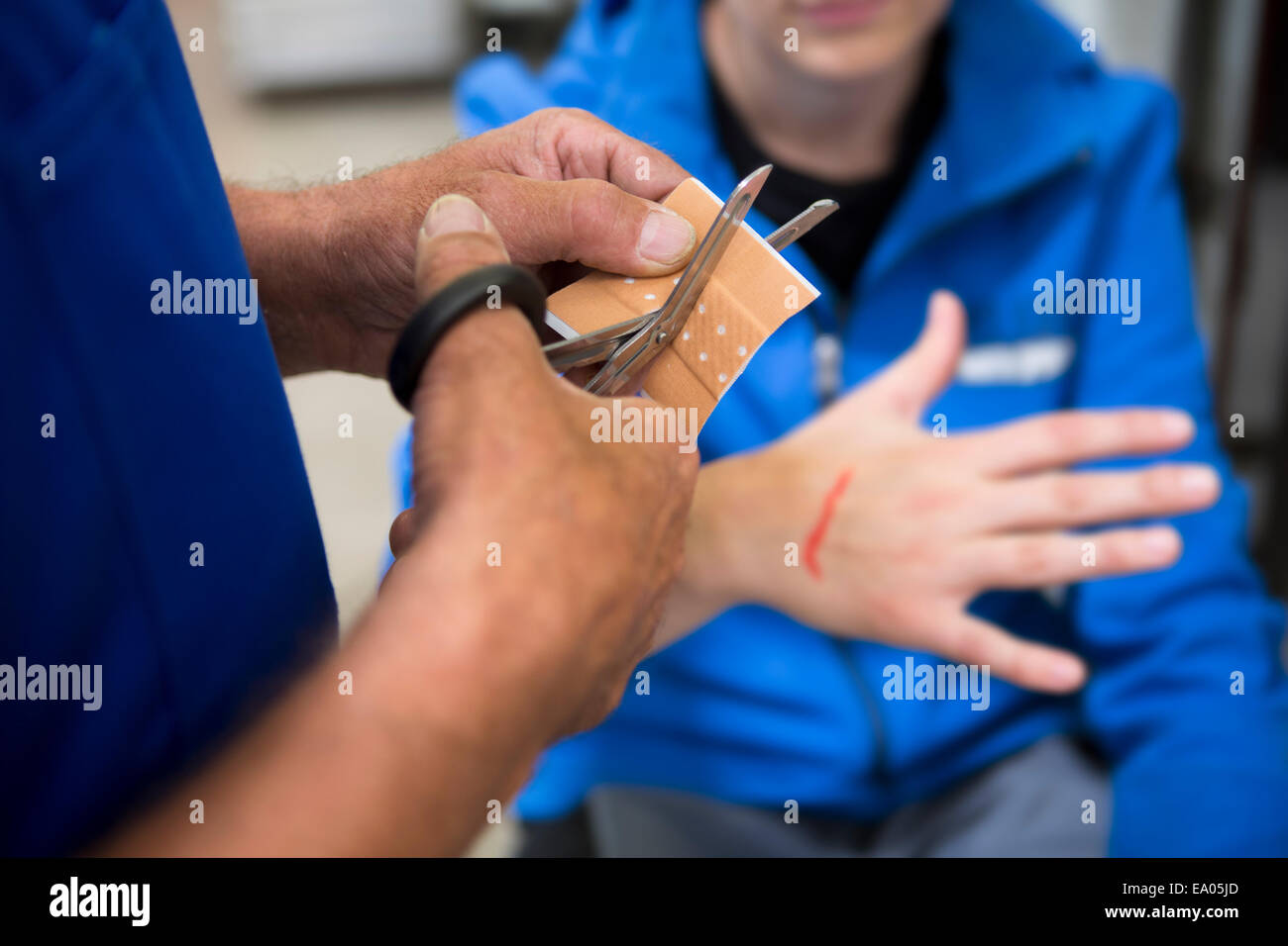 Factory worker applying first aid to colleague - Stock Image
