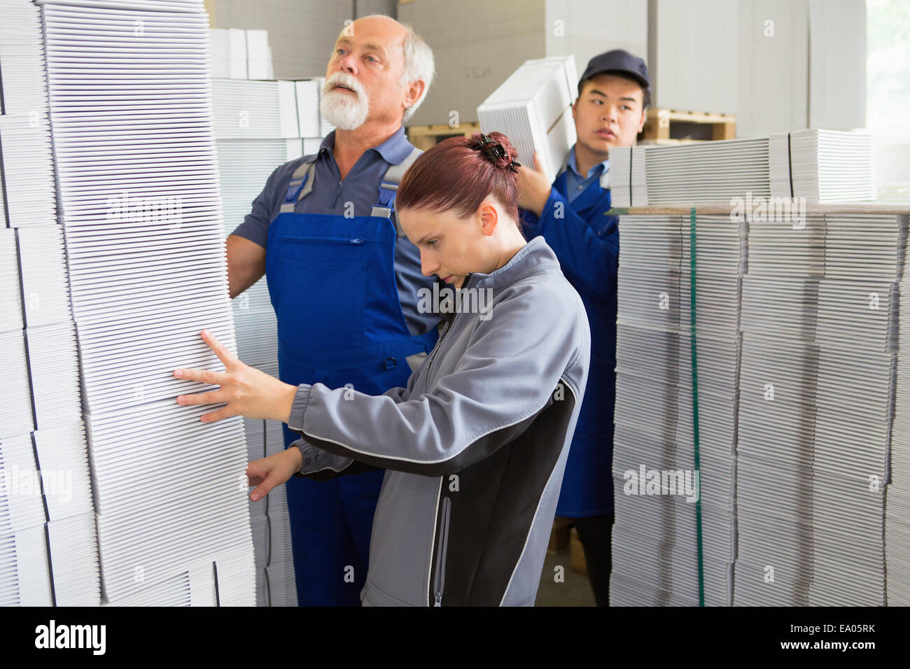 Factory workers moving and stacking cardboard - Stock Image