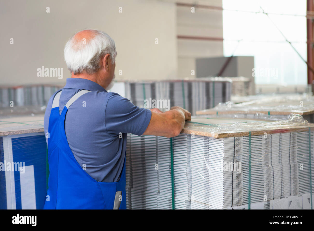 Factory worker moving and stacking cardboard - Stock Image