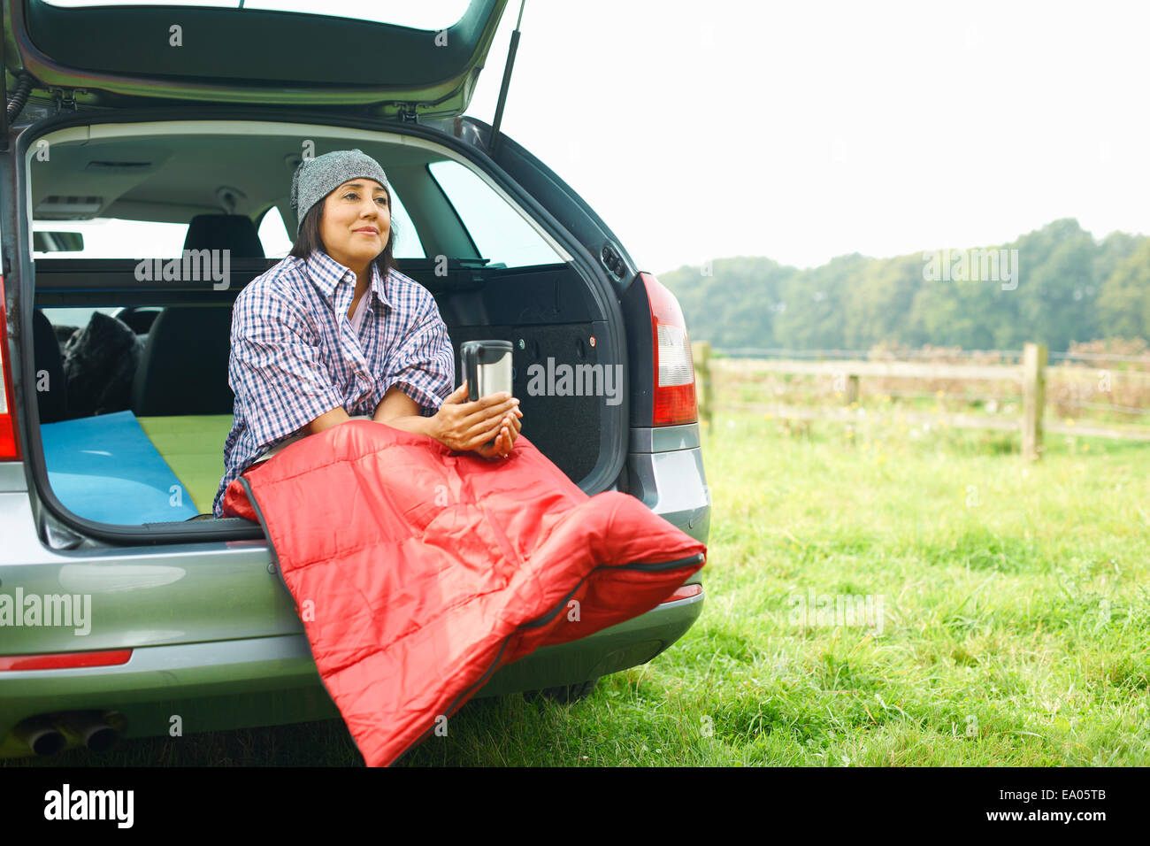 Woman sitting at rear of car with legs tucked in sleeping bag - Stock Image