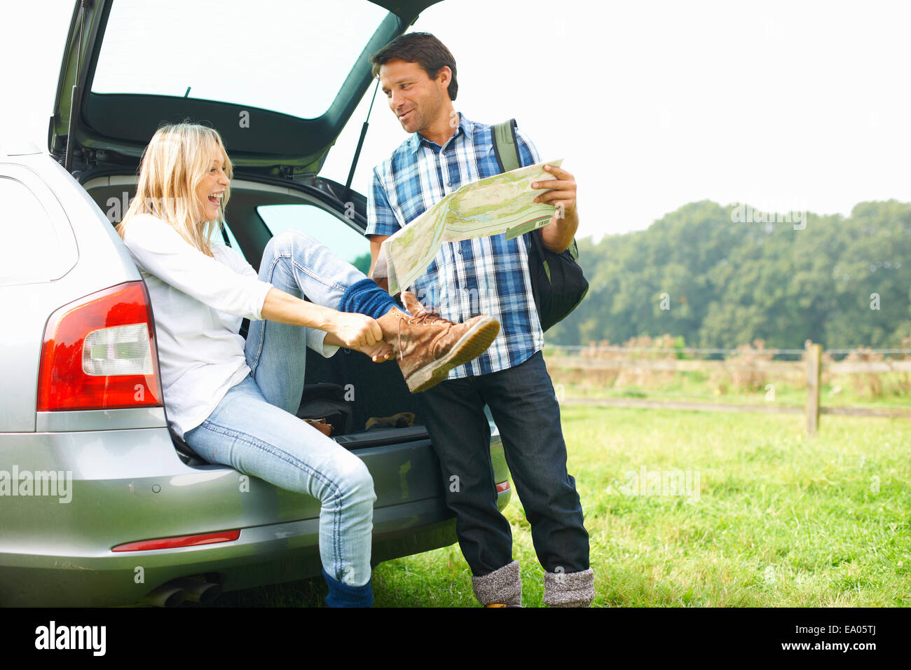 Couple at rear of car map reading preparing for walk - Stock Image