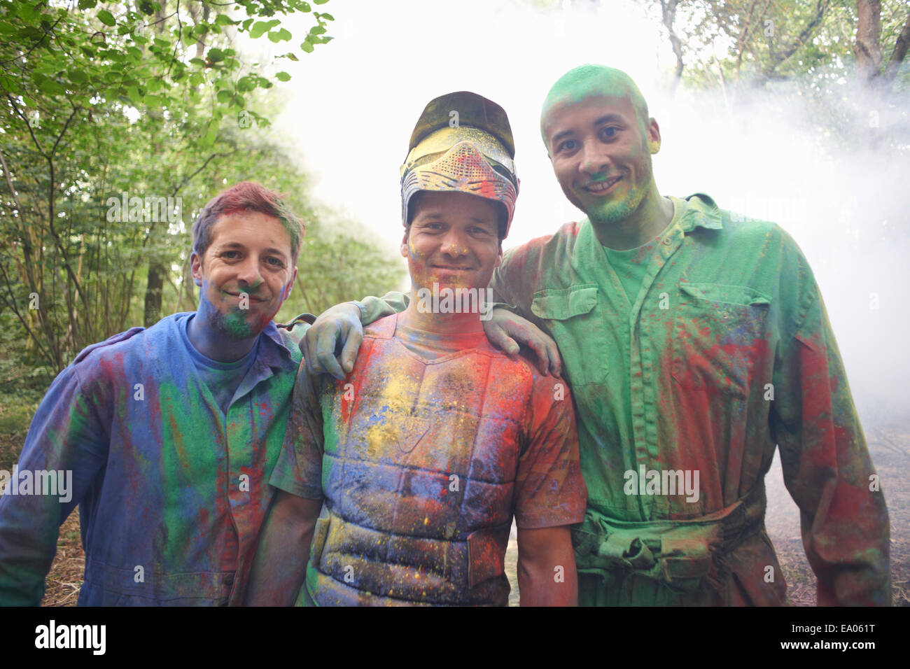 Paintball players in paintball wear marked with paint - Stock Image