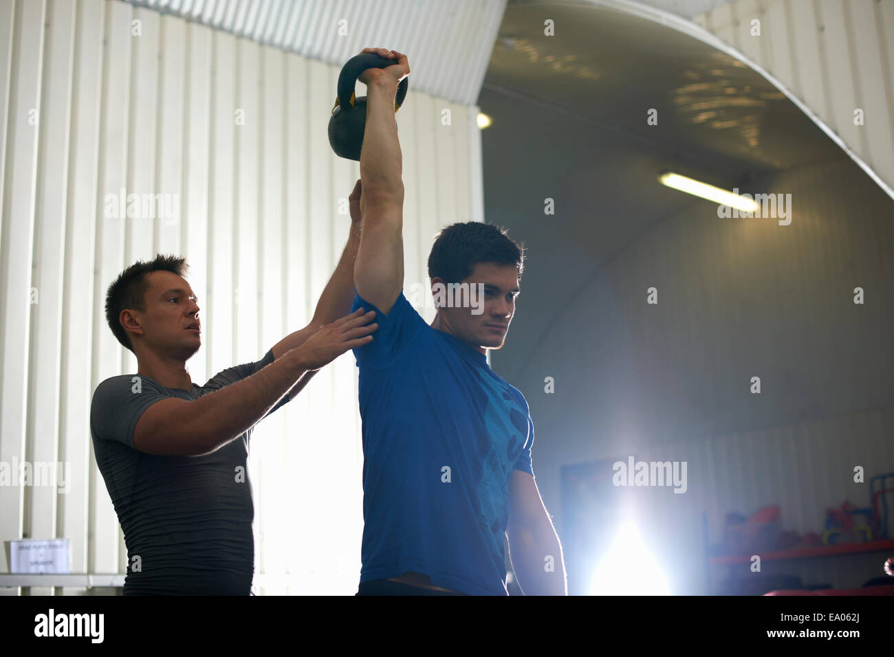 Trainer coaching man with kettlebell in gym Stock Photo