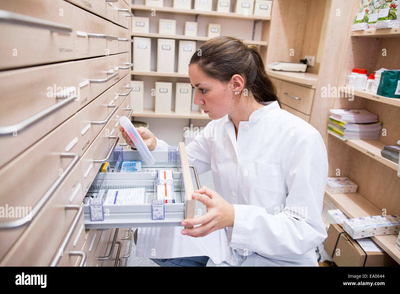 Pharmacist in pharmacy opening medicine file drawer - Stock Image