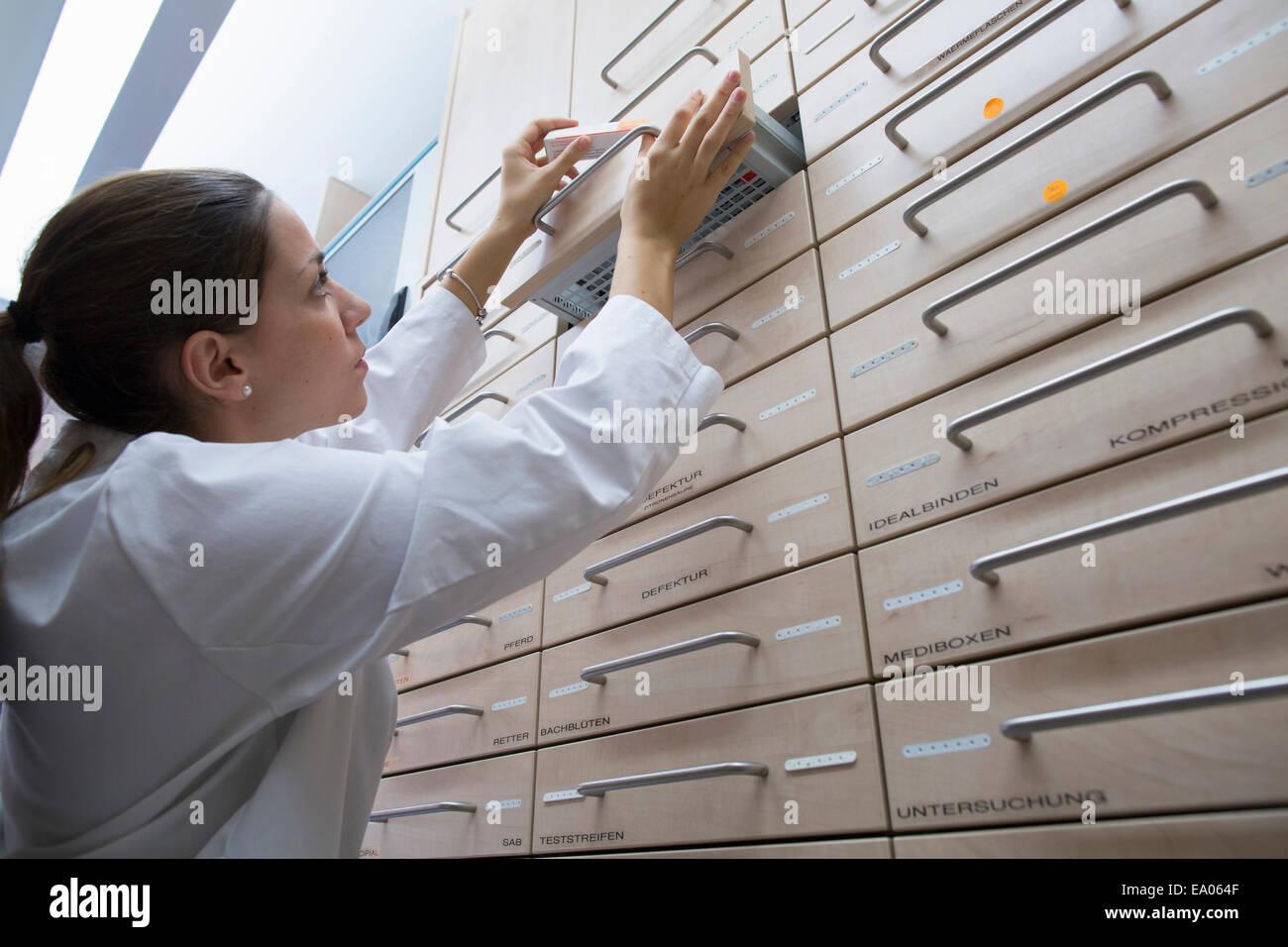 Pharmacist in pharmacy filing medicine away in drawer - Stock Image