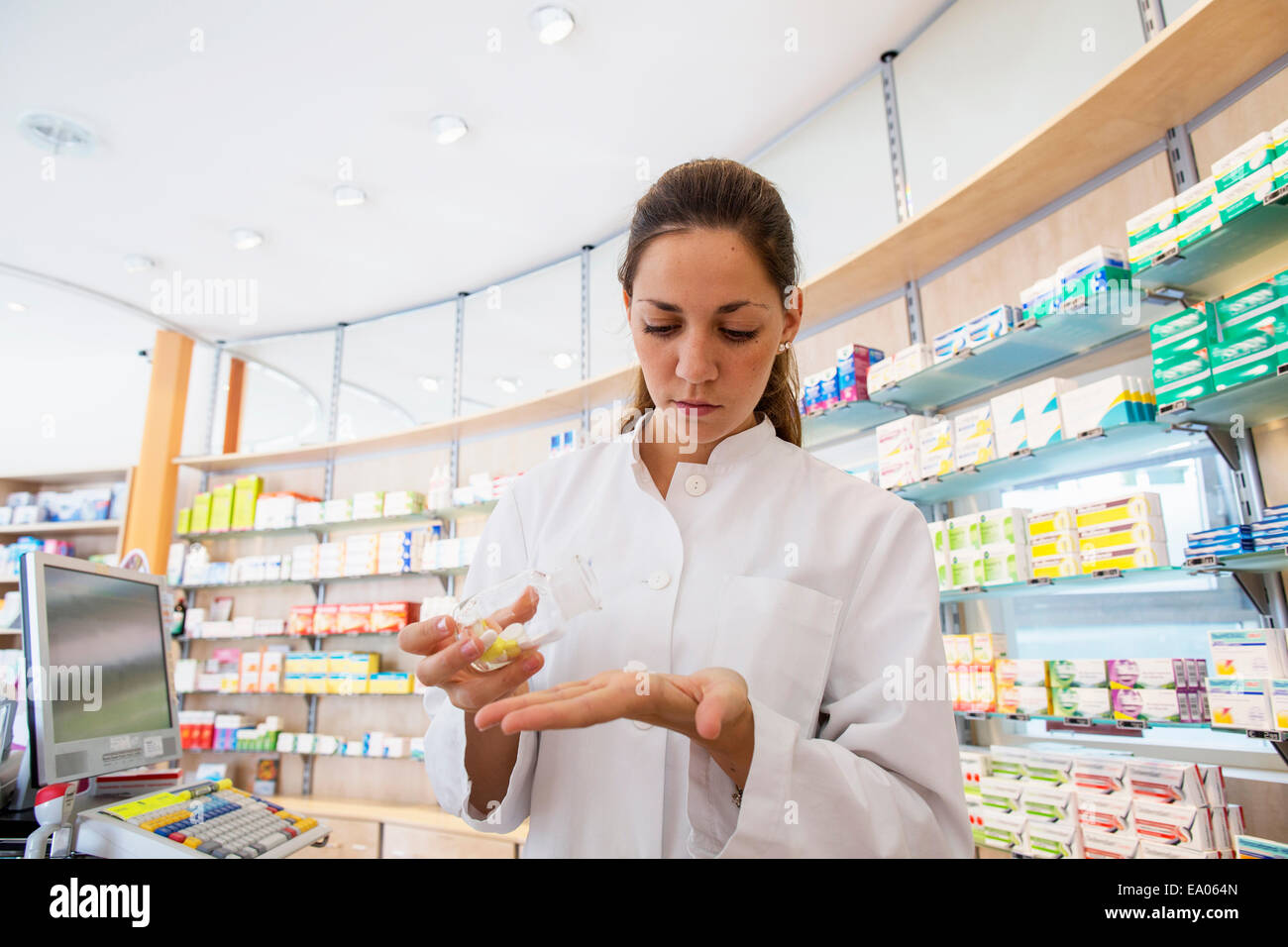 Pharmacist in pharmacy holding medicine in hand - Stock Image