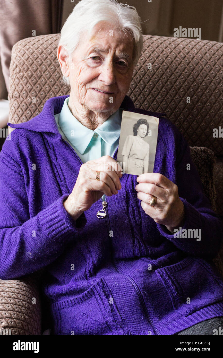 elderly lady holding a photograph of her younger self. - Stock Image