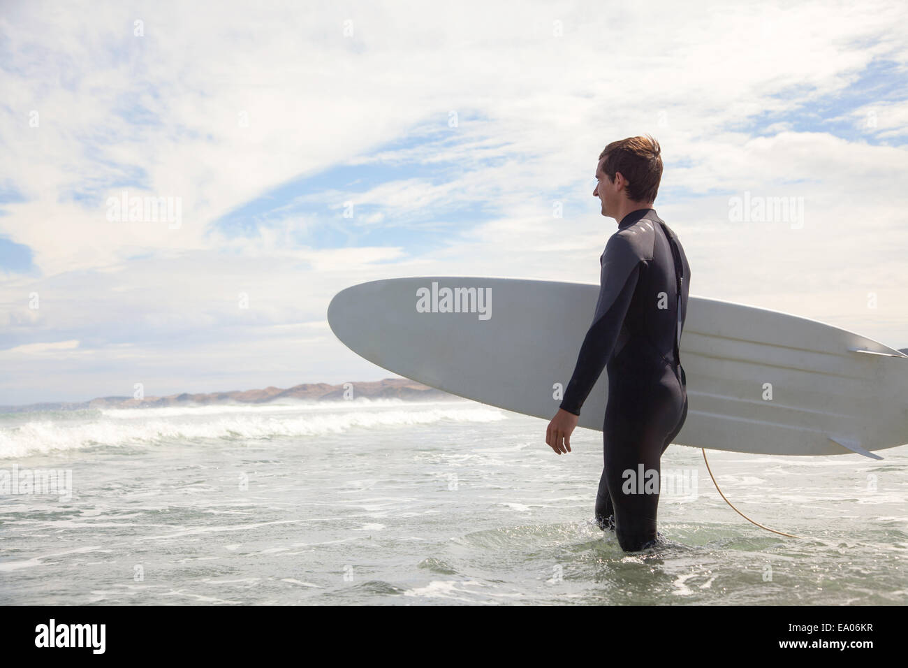 Young man carrying surfboard, walking out to sea - Stock Image
