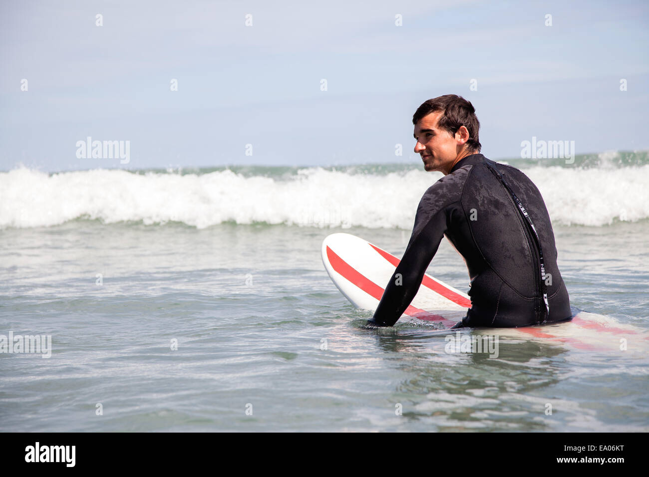 Young man sitting on surfboard in sea Stock Photo