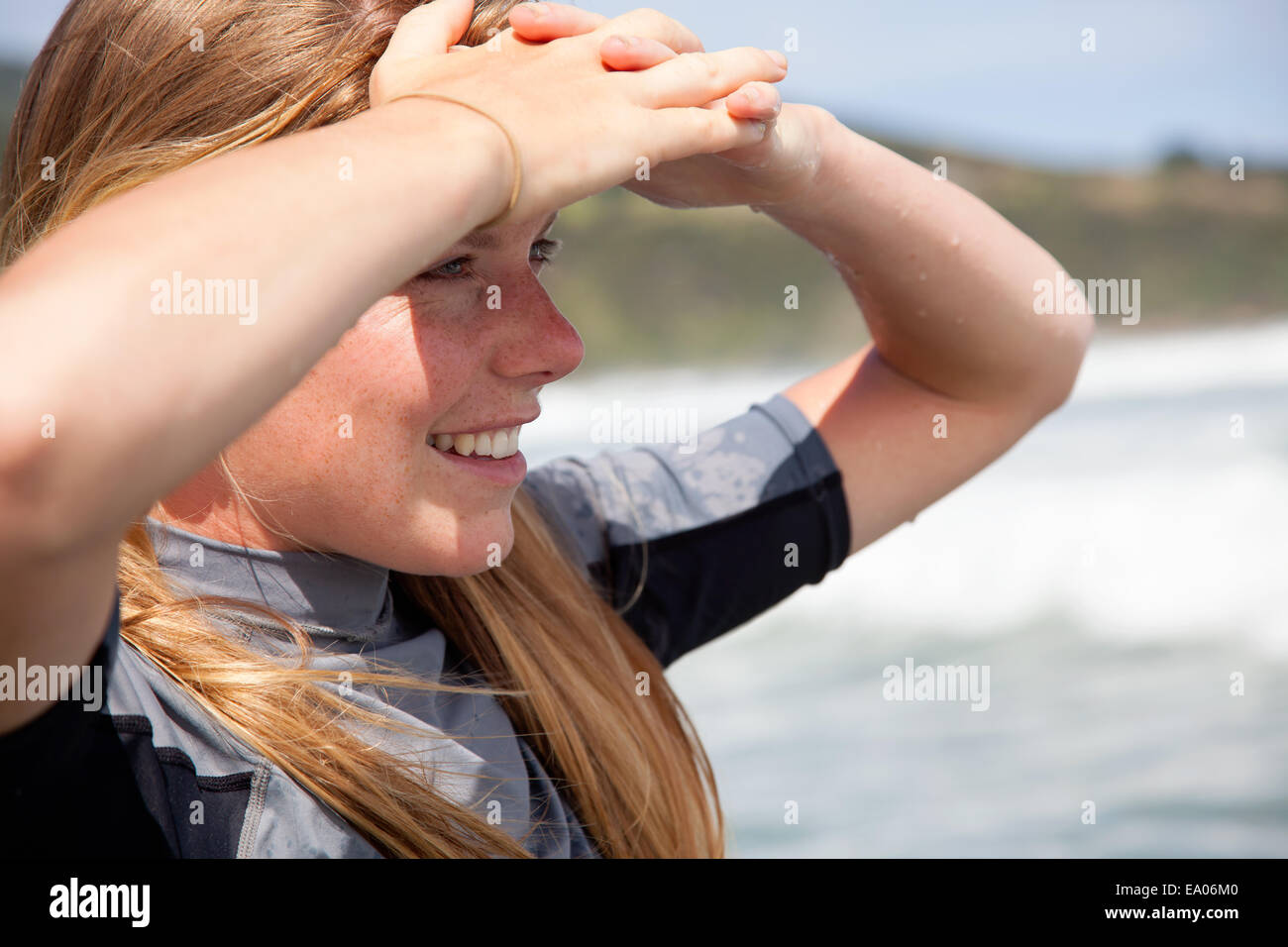 Portrait of young woman wearing wetsuit, looking out to sea Stock Photo