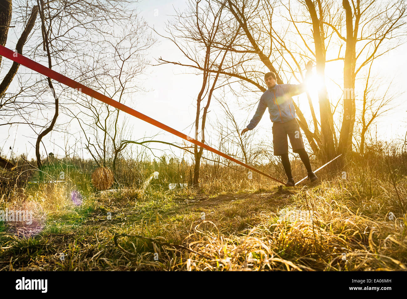 Young man balancing on one leg on slackline in field landscape - Stock Image