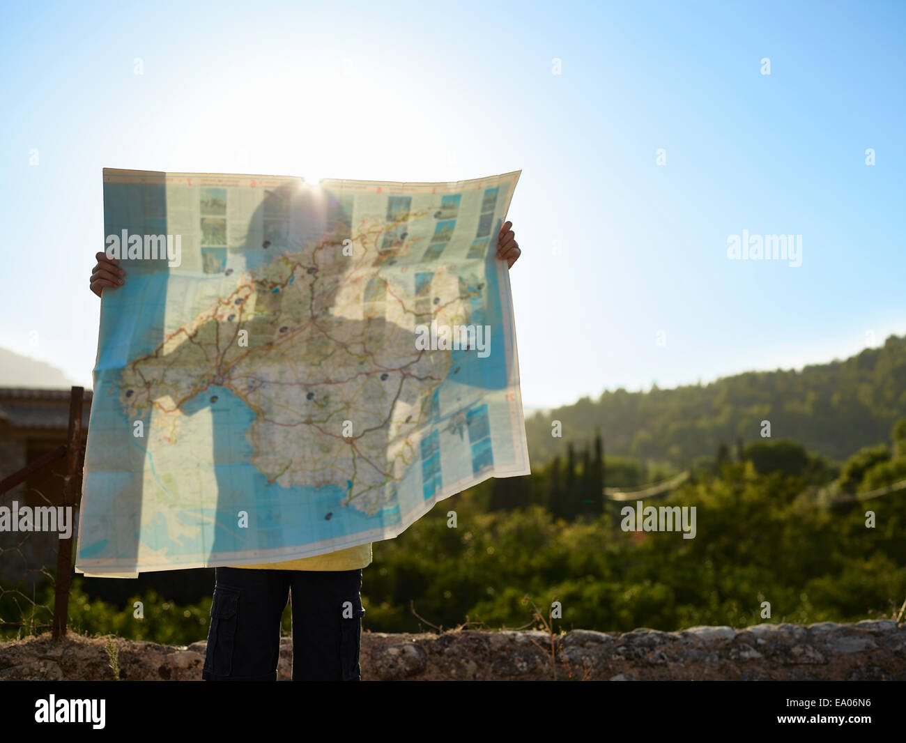 Shadow of boy holding up a map, Majorca, Spain - Stock Image