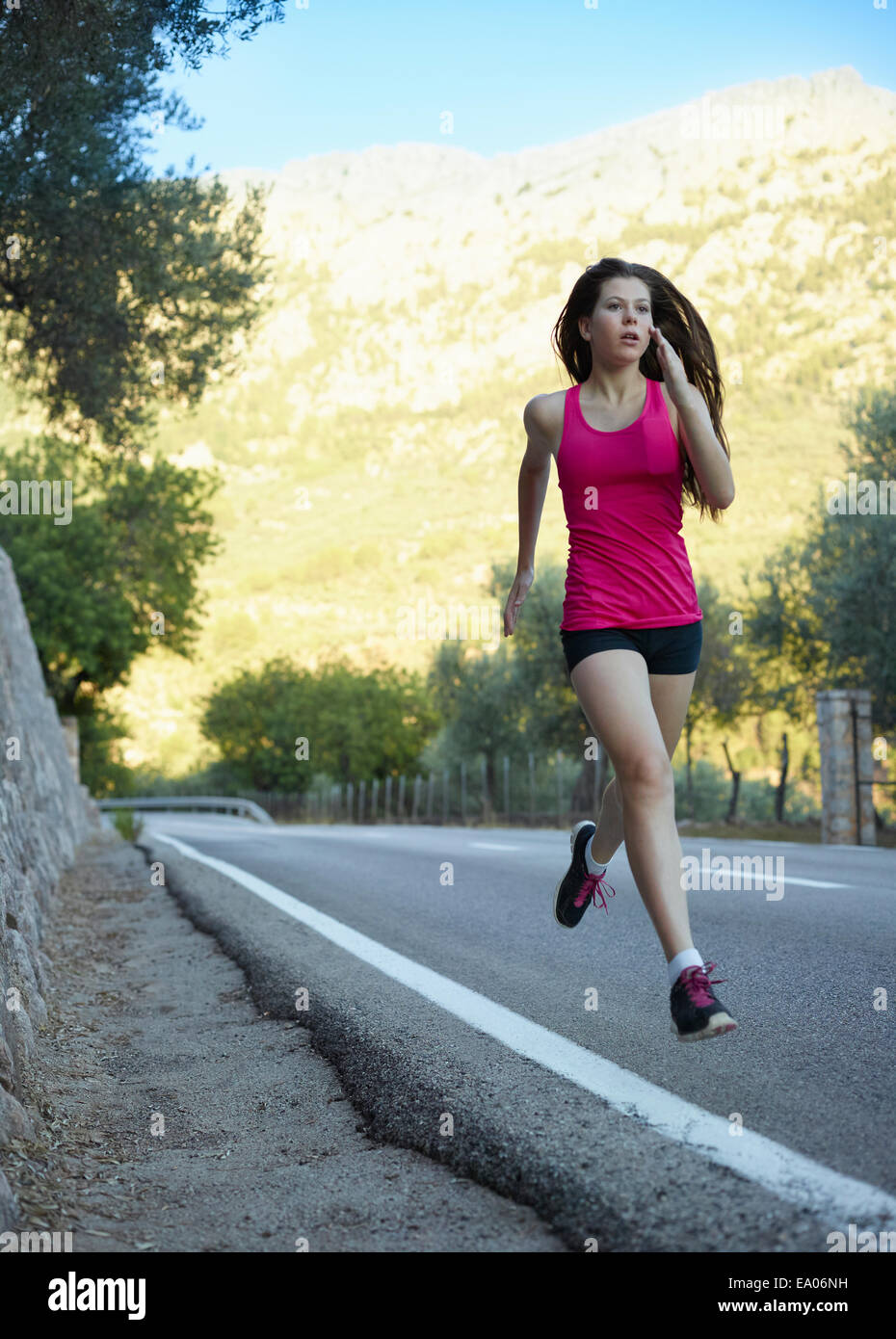 Teenage girl running on road, Majorca, Spain - Stock Image