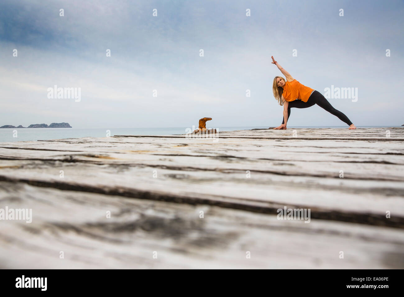 Mid adult woman practicing yoga position on wooden sea pier - Stock Image