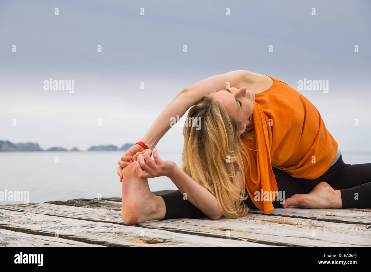 Mid adult woman touching toes practicing yoga on wooden sea pier - Stock Image