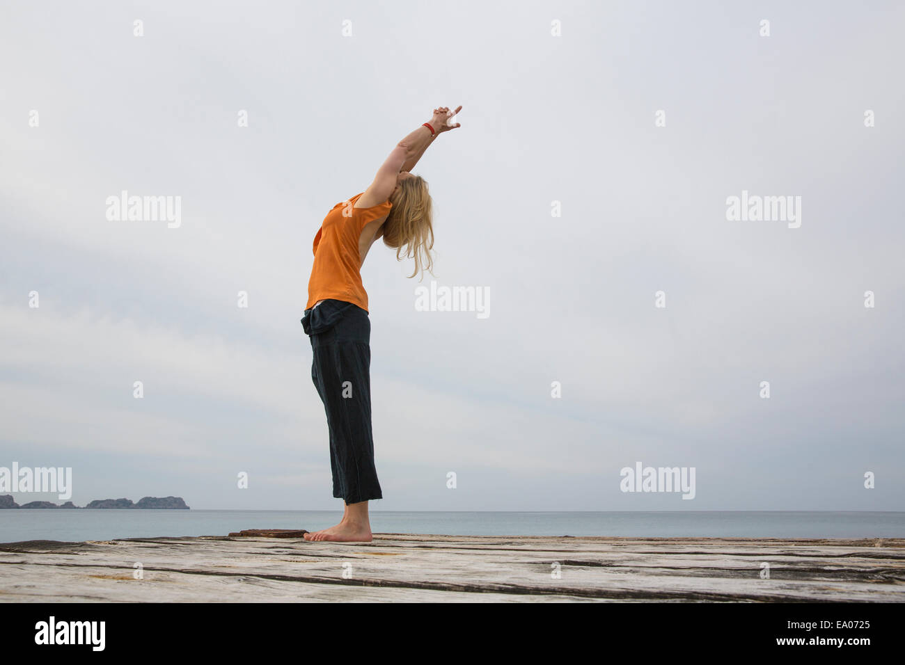 Mid adult woman stretching back practicing yoga on wooden sea pier - Stock Image
