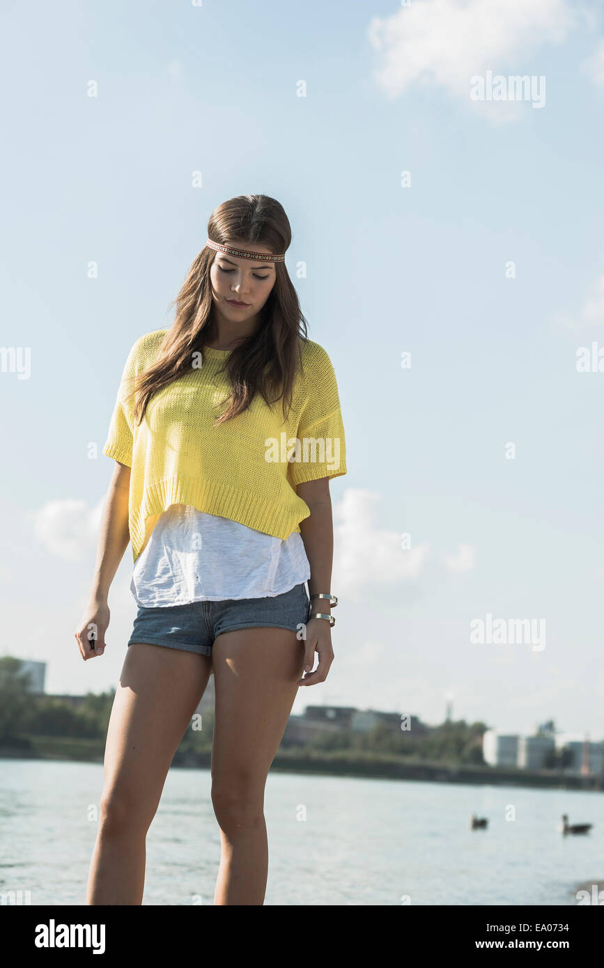 Young woman wearing yellow top and hot pants - Stock Image
