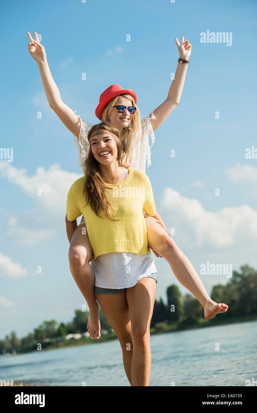 Young woman giving friend piggy back - Stock Image