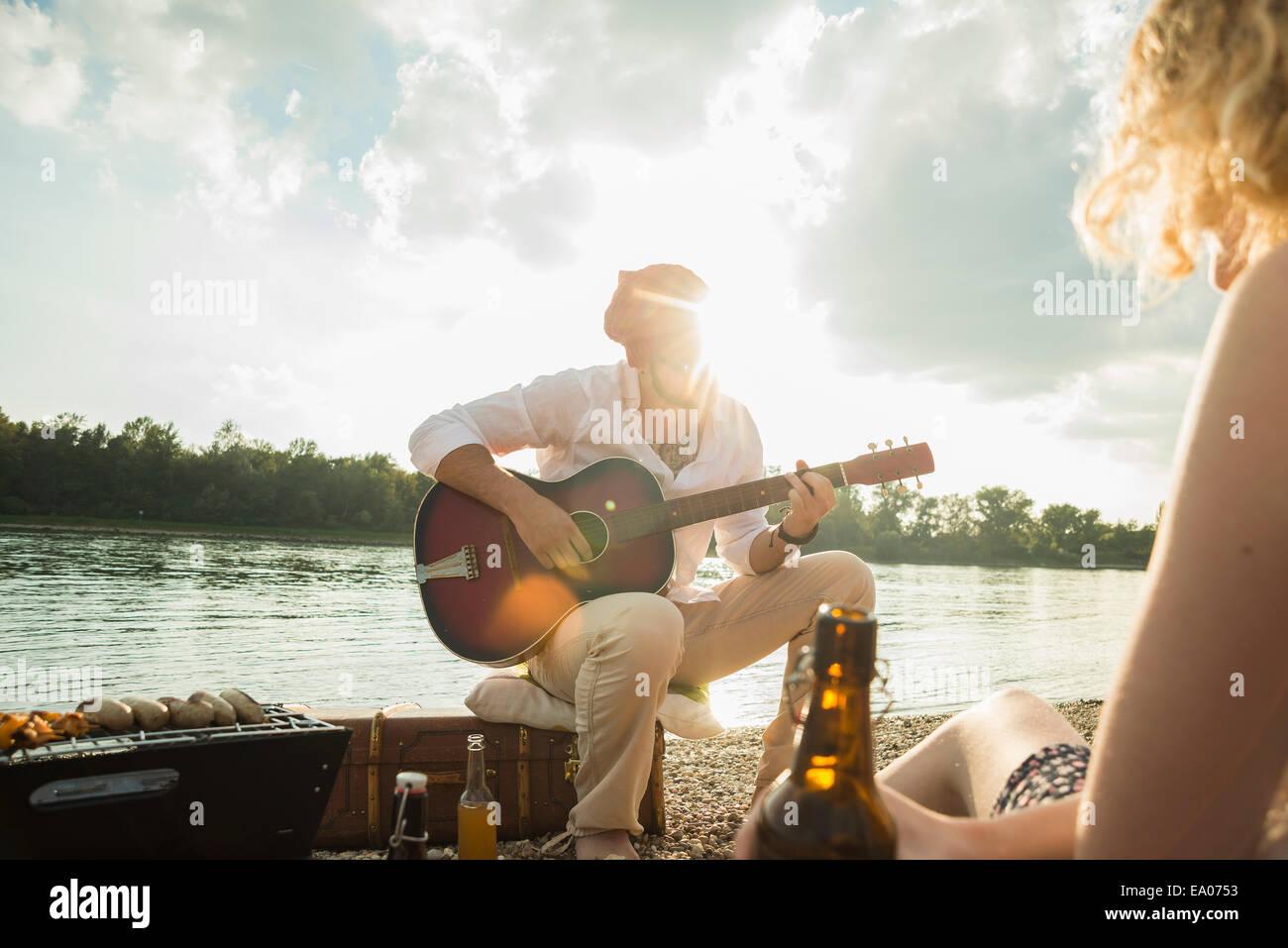 Young man sitting by lake playing guitar - Stock Image