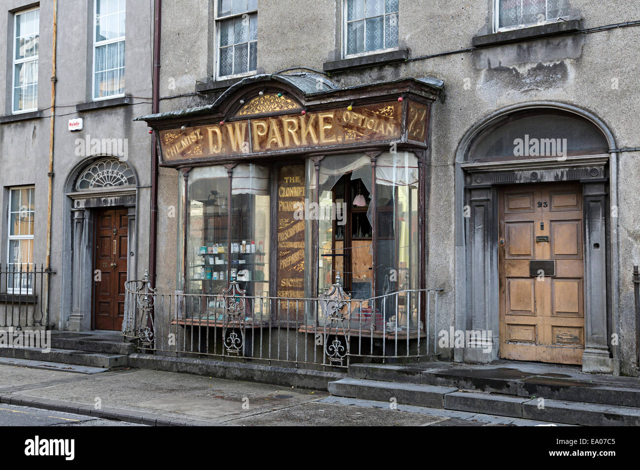 Old chemist and optician shop now closed in street in Clonmel, Ireland - Stock Image