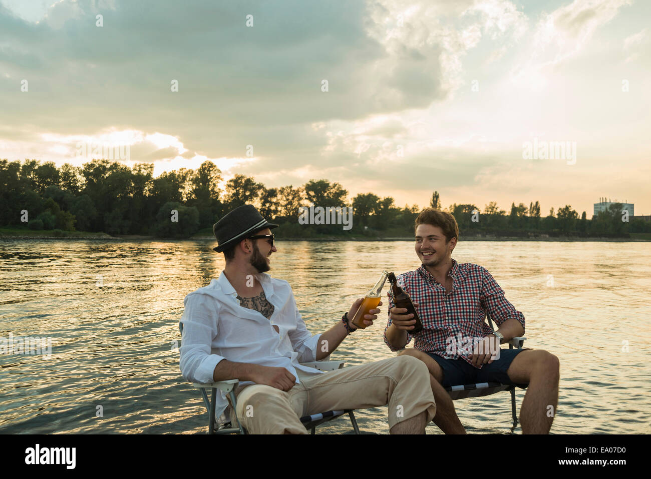 Young men toasting with beer bottles by lake - Stock Image