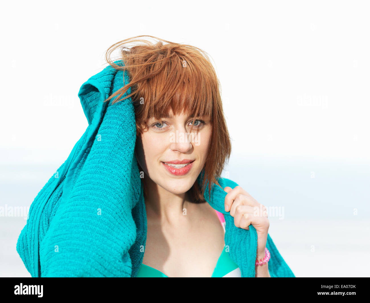 Young woman in bikini drying hair with towel - Stock Image