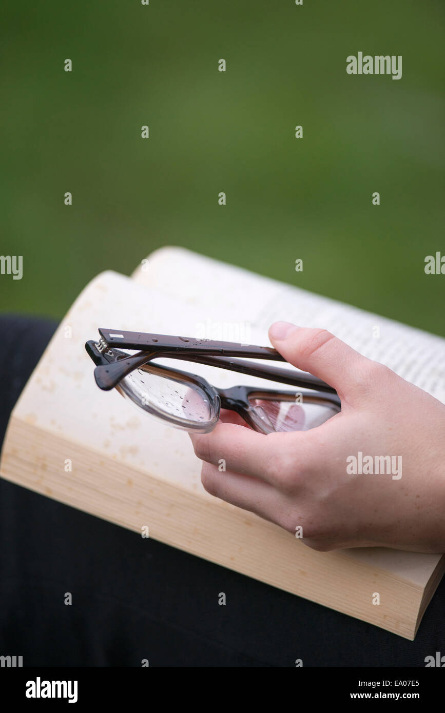 Hand with eye glasses keeping book open - Stock Image