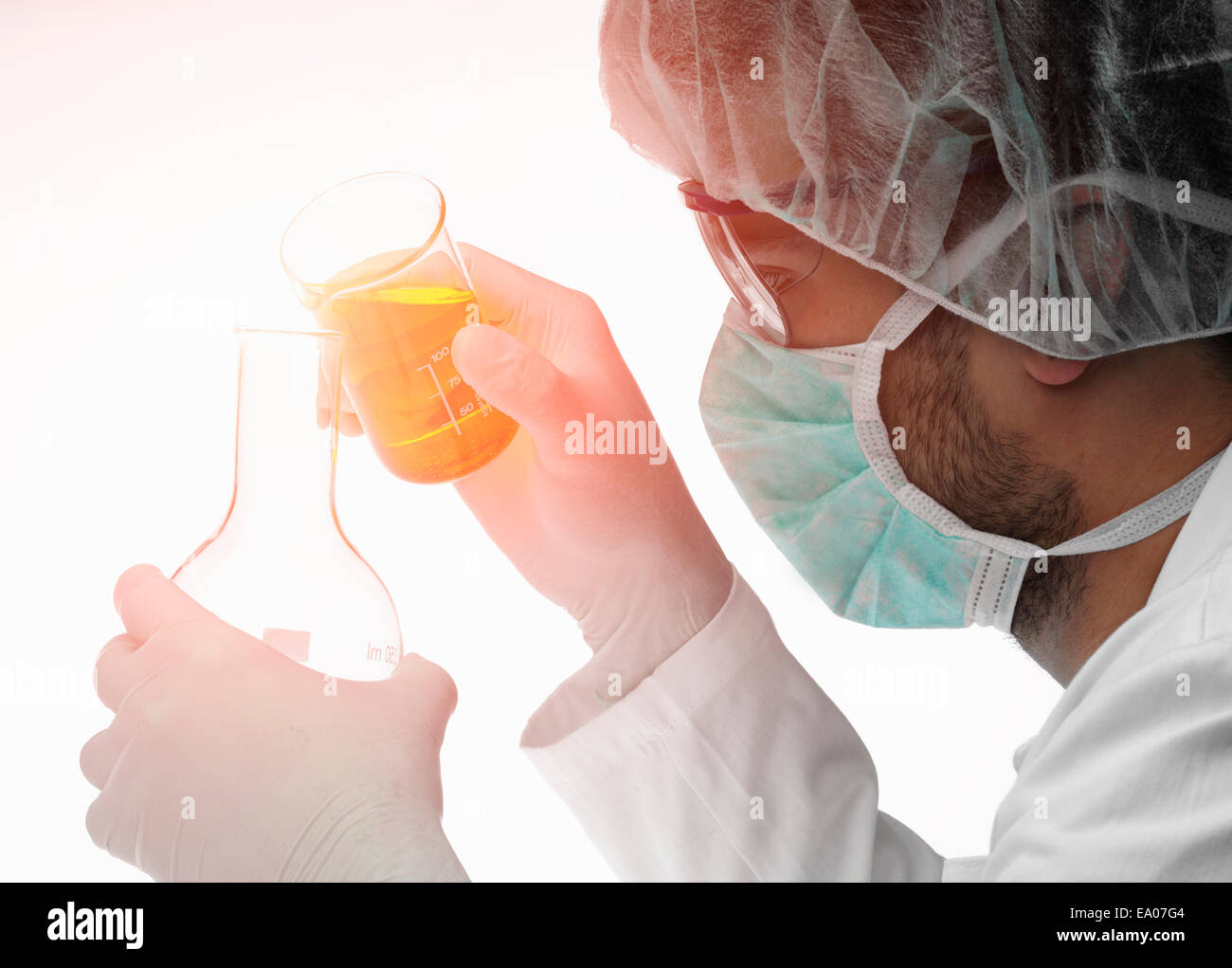 Chemist pouring liquid from beaker into flask - Stock Image