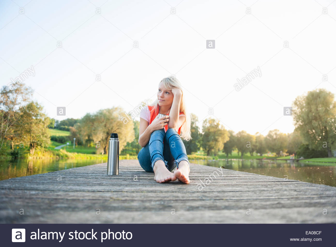 Young woman sitting on pier with drinks flask - Stock Image