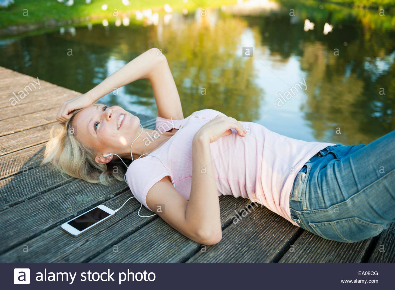 Young woman lying on pier with mp3 player - Stock Image