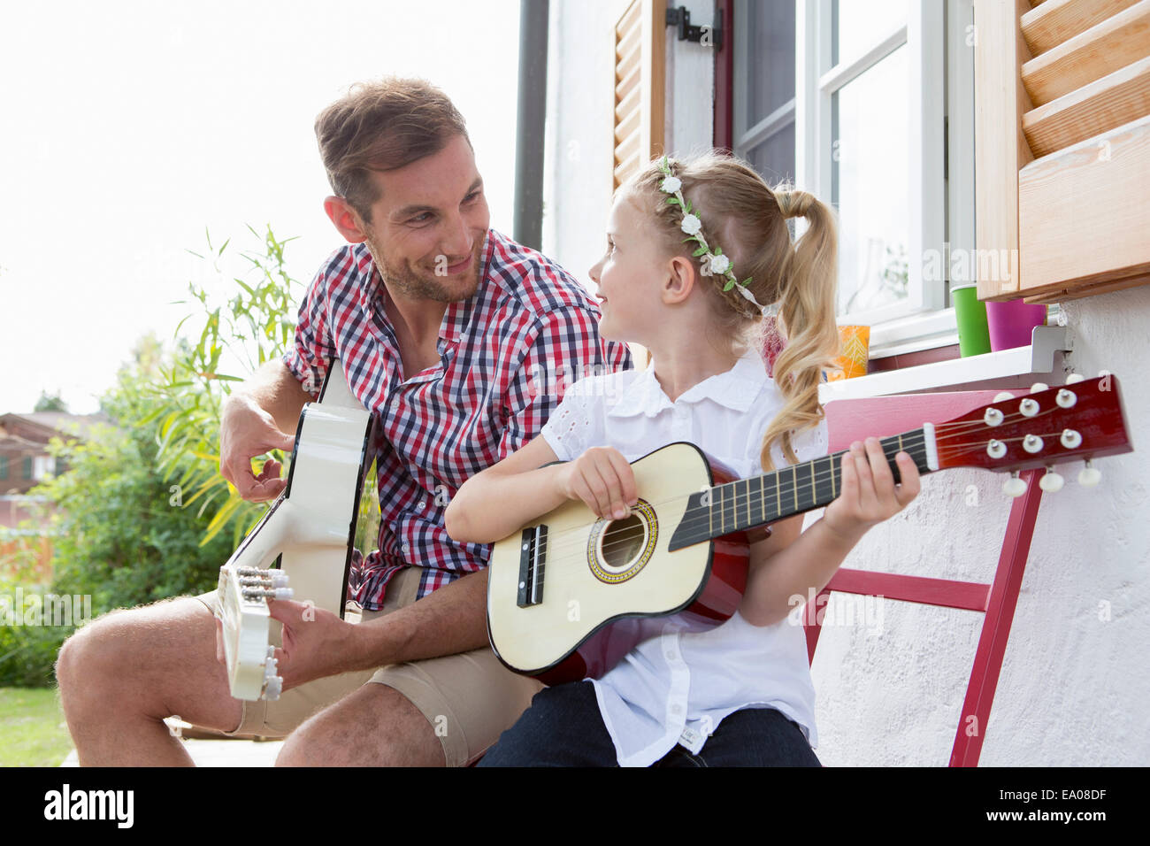 Girl playing guitar with father - Stock Image