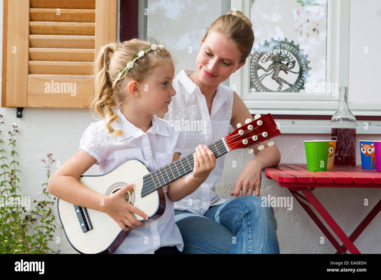 Girl playing guitar with mother - Stock Image