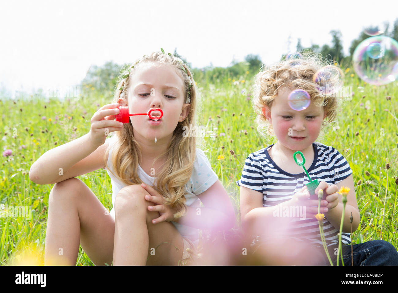 Two girls blowing bubbles - Stock Image