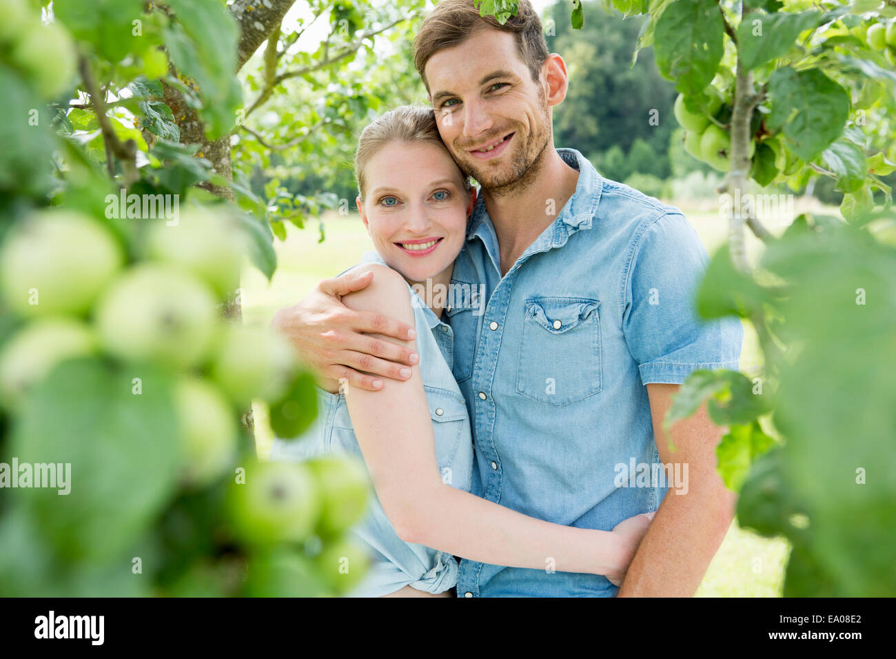 Mid adult couple with arms around each other - Stock Image