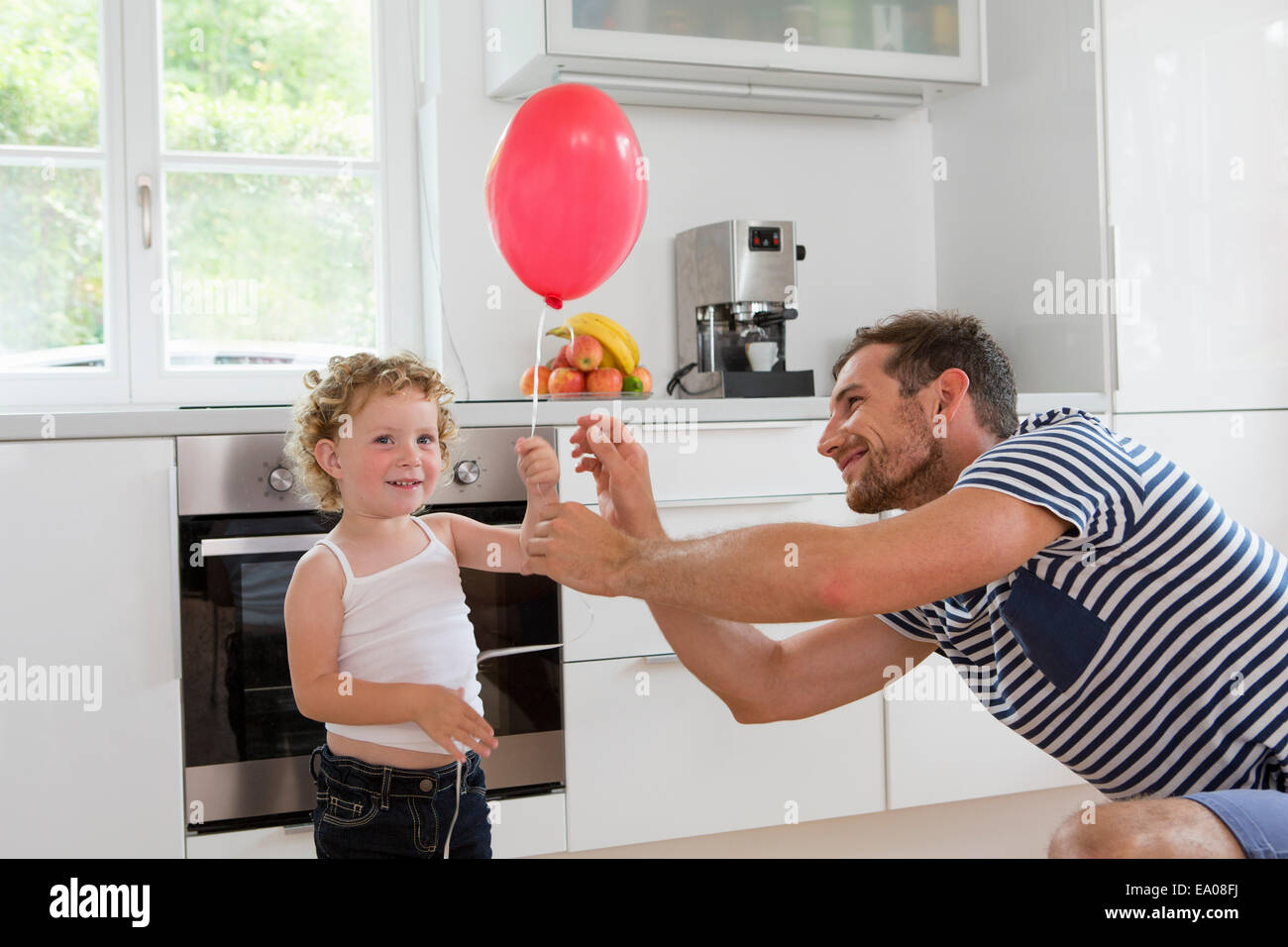 Girl holding balloon with father in kitchen - Stock Image