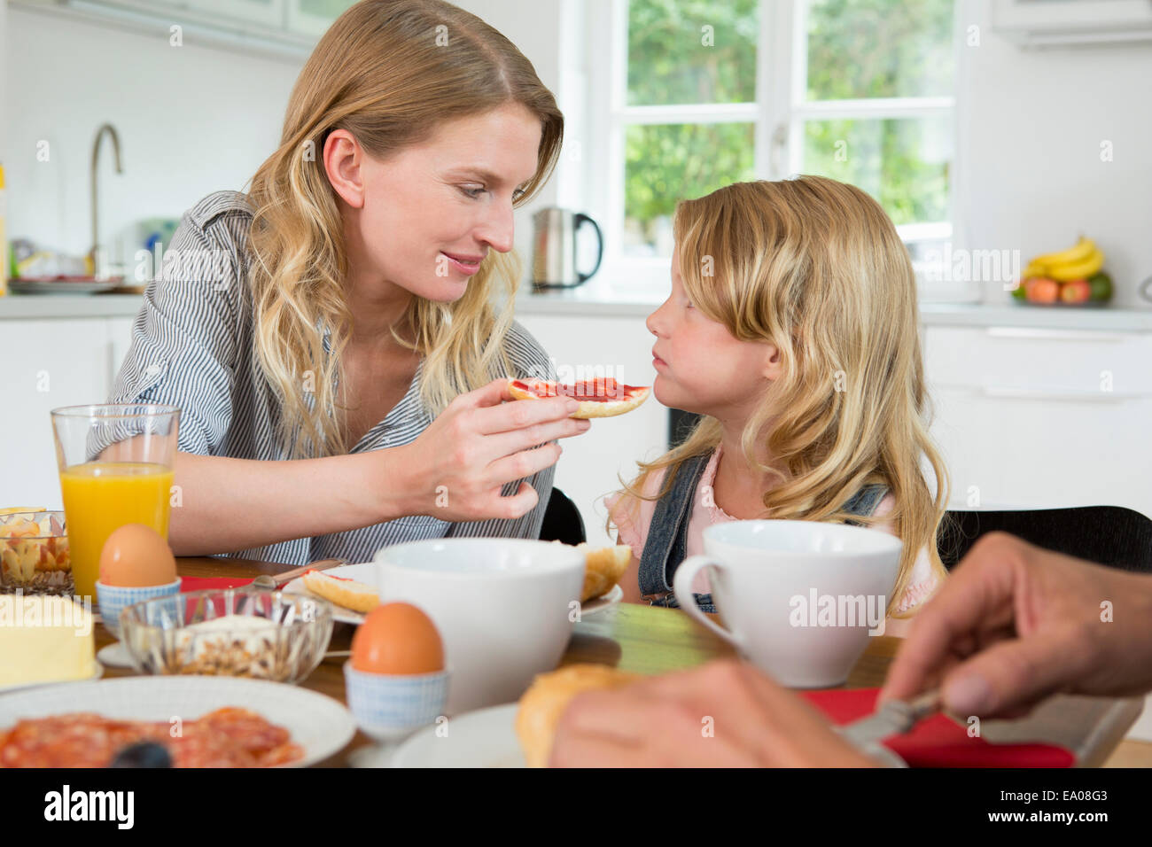 Mother offering daughter some food - Stock Image