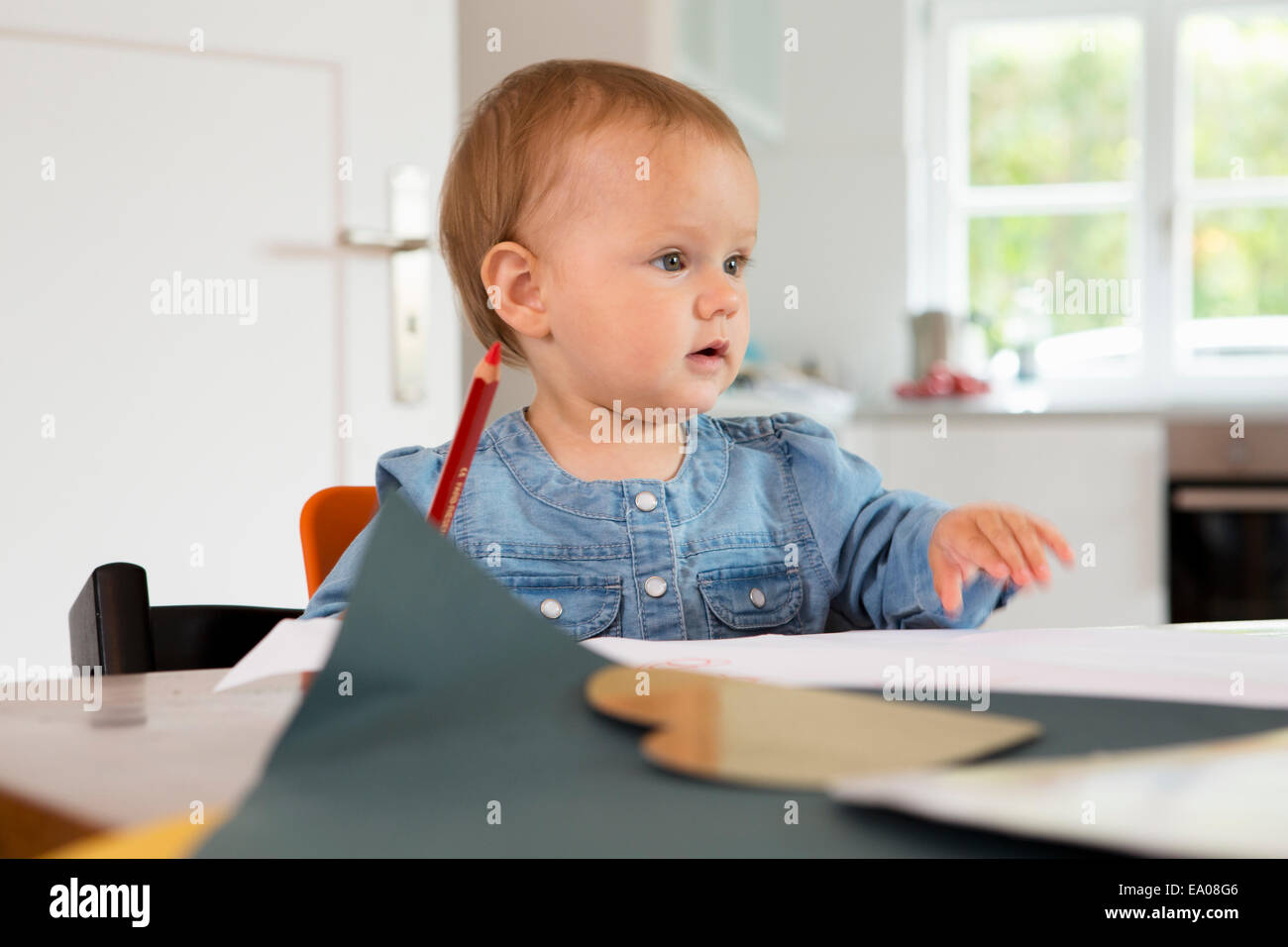 Baby girl with pencil and paper - Stock Image