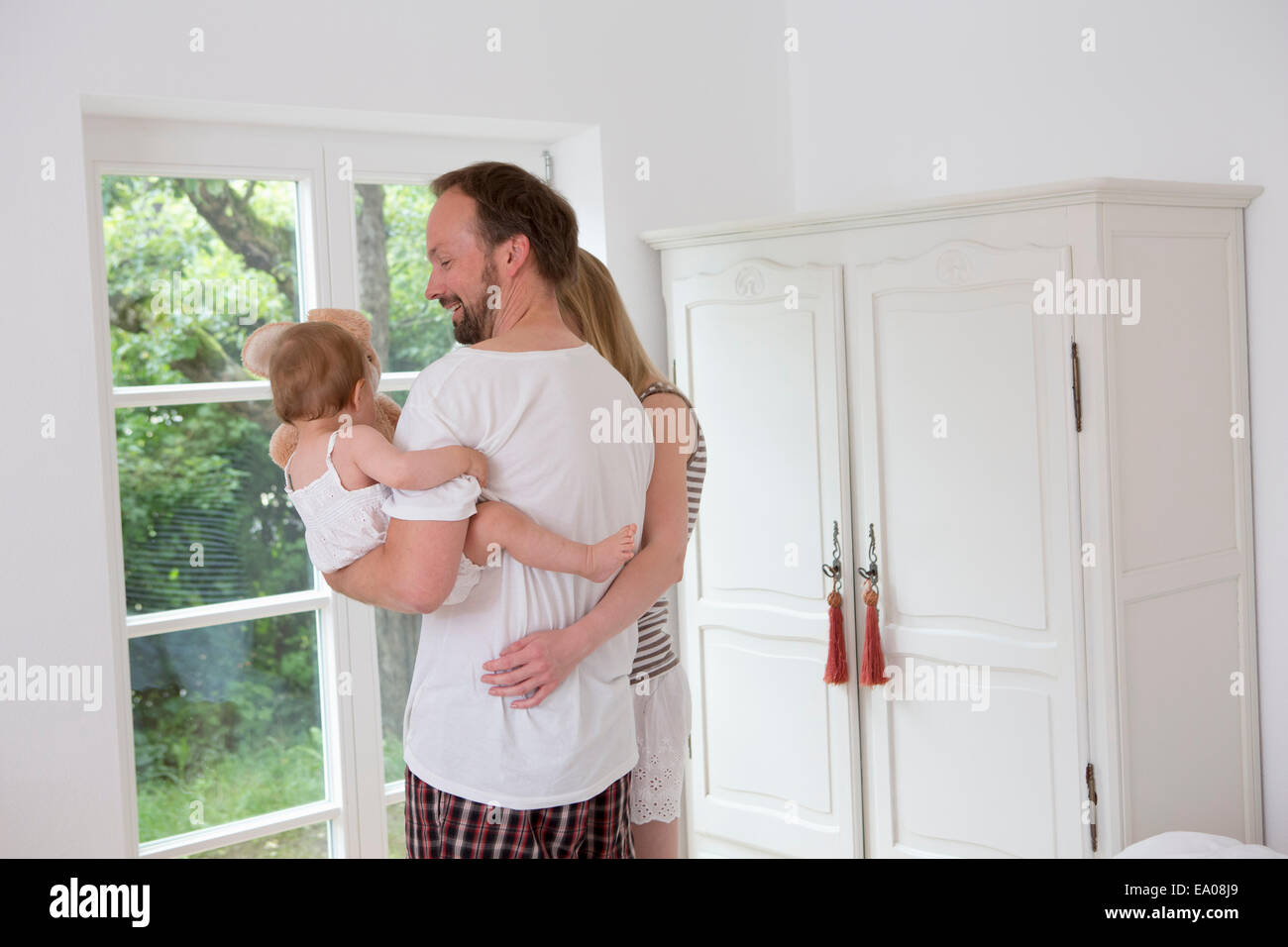 Father holding baby daughter, woman with arm around man - Stock Image