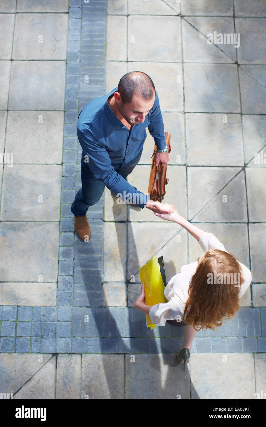 Businessman and business woman shaking hands - Stock Image