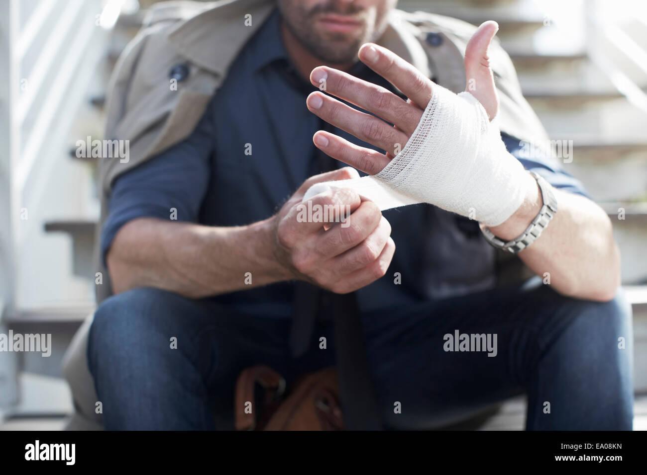 Man bandaging hand on staircase - Stock Image