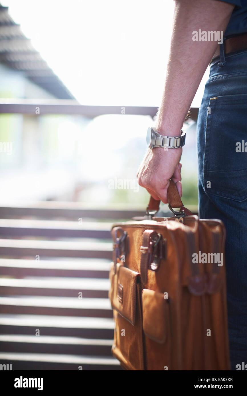 Businessman carrying briefcase - Stock Image