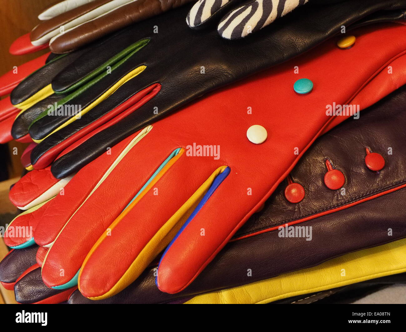 Display of brightly coloured colored overlapping high quality leather gloves - Stock Image