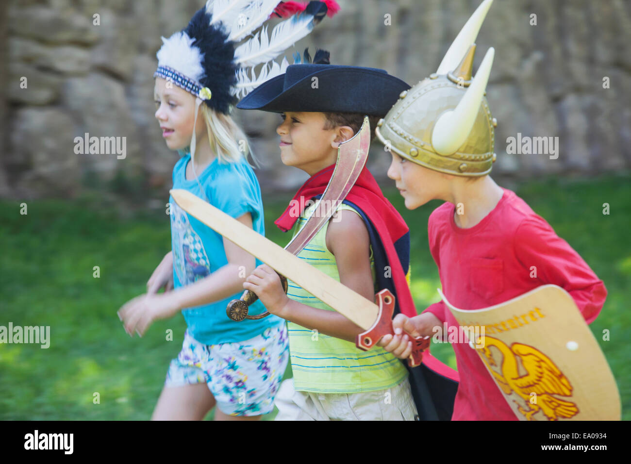 Three children wearing fancy dress costumes, playing in park - Stock Image