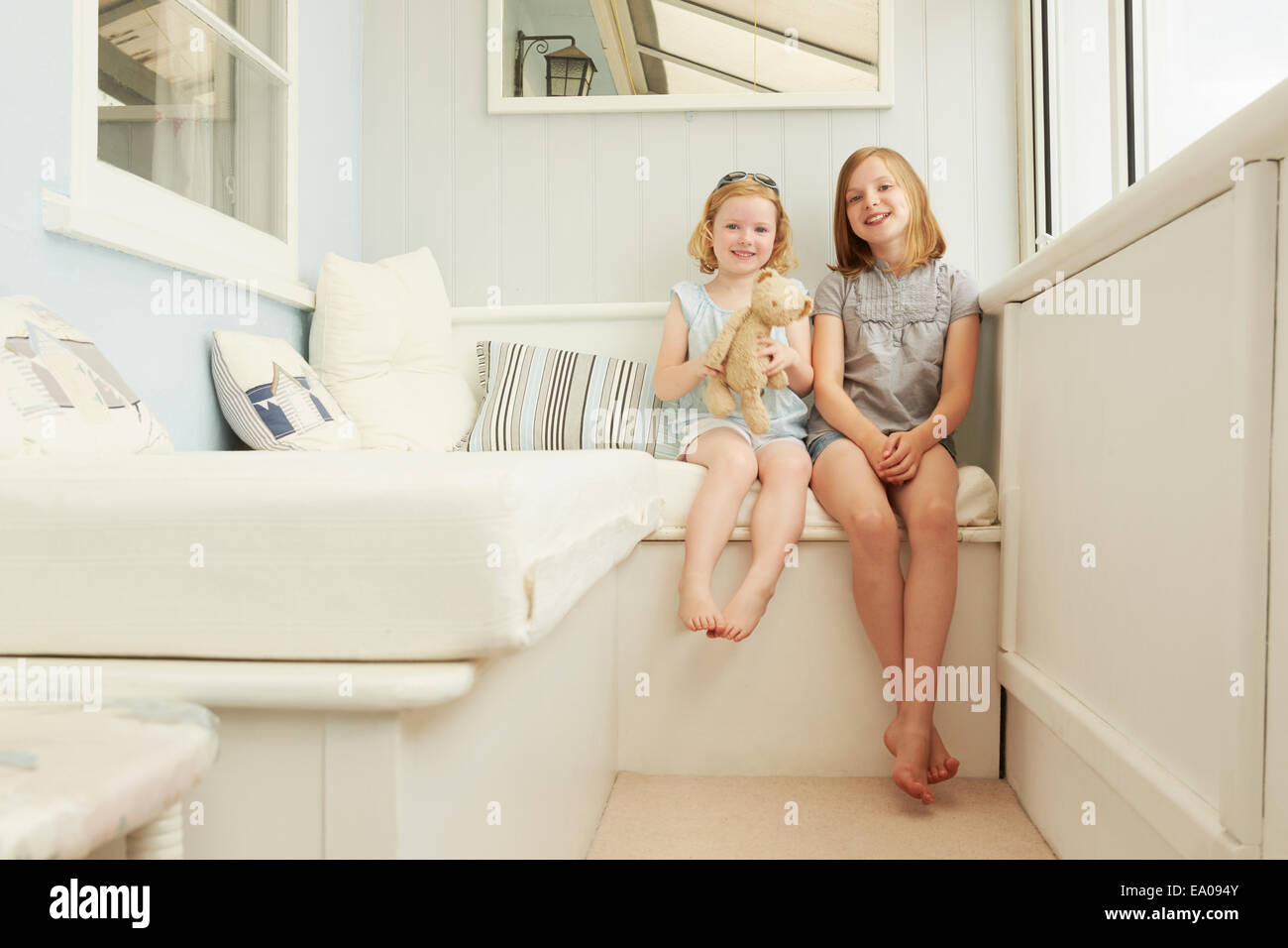 Portrait of two sisters sitting in holiday apartment porch - Stock Image